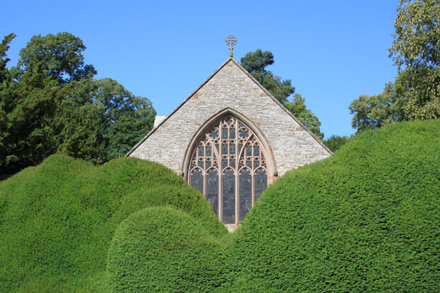 The east window of the church peeking above the hedge.